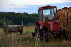 有站立在领域的拖车的红色拖拉机 免版税库存照片