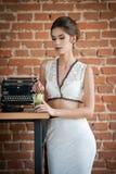 有站立在餐馆桌附近的白色礼服的时兴的可爱的夫人喝一杯 深色的头发短小妇女 库存照片