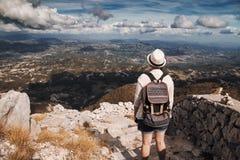 有站立在高山的背包的妇女旅客 免版税库存图片