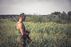 有站立在高芦苇草的农村领域的猎枪的猎人人在狩猎期期间在热的夏日 免版税图库摄影
