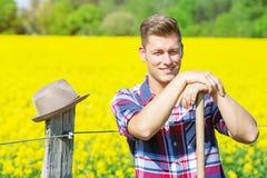 有站立在黄色领域前面的干草叉的英俊的人 库存图片