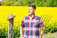 有站立在黄色领域前面的干草叉的英俊的人 免版税图库摄影