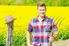 有站立在黄色领域前面的干草叉的英俊的人 免版税库存照片