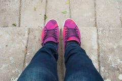 有站立在水泥地板上的蓝色牛仔裤和甜桃红色鞋子的女孩 免版税库存照片