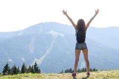有站立在cliff& x27的背包的少妇; s边缘和看对天空用被举的手,您的文本的自由空间 库存照片