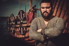 有站立在drakkar附近的轴的北欧海盗在海滨 库存图片
