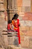 有站立在Quwwat Ul回教清真寺, Qu的孩子的印地安妇女 库存照片