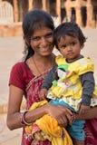 有站立在Quwwat Ul庭院里的孩子的印地安妇女  免版税库存照片