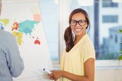 有站立在whiteboard的男性同事的女实业家近的世界地图 免版税库存照片