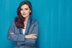 有站立对蓝色墙壁的长的头发的女商人 免版税图库摄影