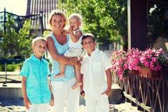 有站立的孩子的愉快的母亲室外 免版税库存照片