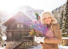 有站立近的山房子的圣诞树的微笑的妇女 免版税库存图片