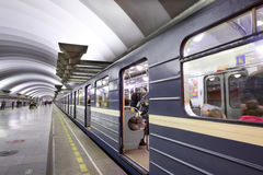 有站立近的平台的乘客的蓝色火车对地铁stat 库存图片