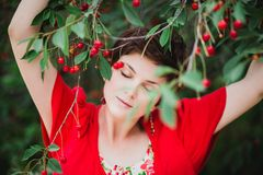 有站立近的樱桃树的短的理发的少妇 免版税库存图片