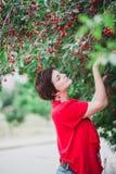有站立近的樱桃树的短的理发的少妇 库存照片