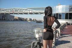 有站立近的河的黑发佩带的礼服的年轻美丽的时髦的女孩在城市街道在一个夏日 库存照片