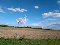 有童话当中风景和cloudscape的电涡轮风车 免版税库存图片