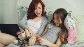 有笑年轻爱恋的母亲的小逗人喜爱的女儿观看滑稽的图片和,当读童话书开会时 股票视频