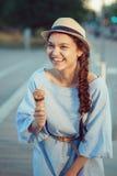 有笑涡的在面颊和被晒黑的皮肤吃冰淇凌的美丽的愉快的白白种人深色的女孩妇女特写镜头画象  免版税库存照片
