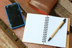 有笔、手机和钱包的笔记本在棕色长凳 免版税图库摄影