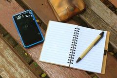 有笔、手机和钱包的笔记本在棕色长凳 库存照片