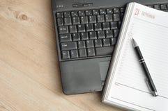 有笔和一本开放日志的一台膝上型计算机 图库摄影