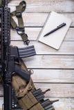有笔和步枪的笔记本 免版税库存照片