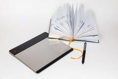 有笔和笔记本的图形输入板 库存图片