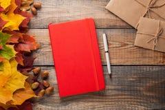 有笔和纸信封的红色笔记本在老木桌上 混杂的槭树秋叶和橡子在一个闭合的笔记本旁边 免版税库存图片