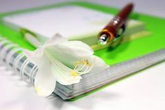 有笔和花的笔记本 免版税库存图片
