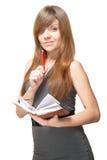 有笔和记事本的微笑的少妇 免版税库存图片