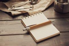有笔和酥皮点心面包店工具的空的白色空间笔记本在木背景 免版税库存照片
