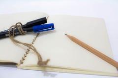 有笔和铅笔的空白的笔记本 免版税库存图片