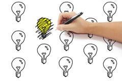有笔图画的手在黄灯电灯泡想法乱写在中 库存照片