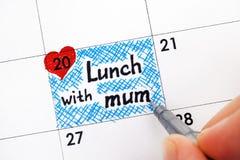 有笔文字提示午餐的妇女手与日历的妈咪 免版税图库摄影