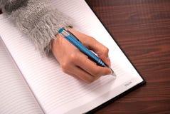 有笔文字的女性手在木书桌上的笔记本 免版税库存图片