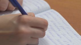 有笔文字的女性手在笔记本 关闭妇女写在螺旋笔记薄的` s手安置在木桌面 股票视频