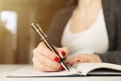 有笔文字的女性手在笔记本 日志,计划,新闻工作者 免版税库存照片