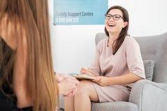 有笔的专业女性治疗师和一个笔记本在她的坐在扶手椅子的手上,当谈话与她时 免版税库存照片