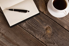 有笔的在木桌上的笔记本和咖啡 免版税库存照片
