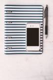 有笔的在白色桌垂直的笔记本和电话 免版税库存图片