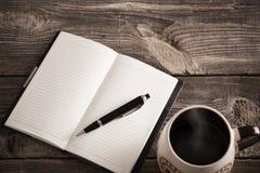 有笔的在老木桌上的笔记本和咖啡 库存图片