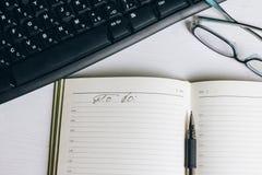 有笔的开放在桌上的笔记本和玻璃 免版税库存照片