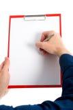 有笔的手书写在剪贴板 库存图片