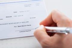 有笔的手在支票簿 免版税库存照片