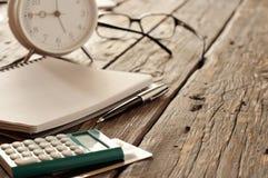 有笔的有信用卡的笔记本,计算器和闹钟 图库摄影