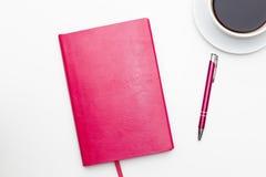 有笔的桃红色笔记本和一杯在白色的无奶咖啡 免版税库存照片
