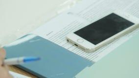 有笔的特写镜头手在笔记本写笔记在智能手机附近 影视素材