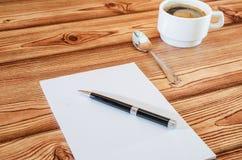 有笔的白色笔记本和咖啡在木背景的 免版税库存图片