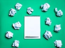 有笔的白色笔记本在纸球中的绿色背景 引起想法的概念,发明新的想法 纸球 免版税库存照片